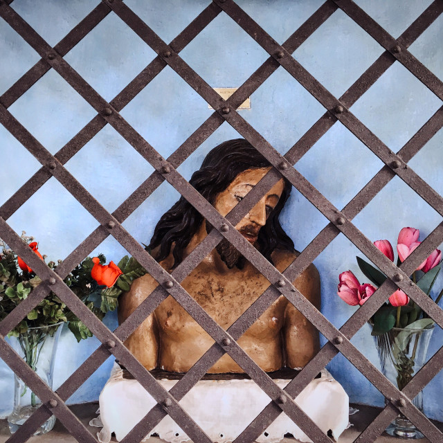 """A caged Jesus amidst the flowers"" stock image"