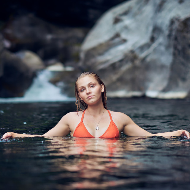 """A Young Woman in a Bikini Standing in a Creek by A Waterfall"" stock image"
