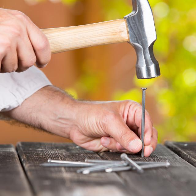 """""""Carpenter nailing a nail"""" stock image"""