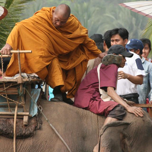 """Monk mounting an elephant"" stock image"
