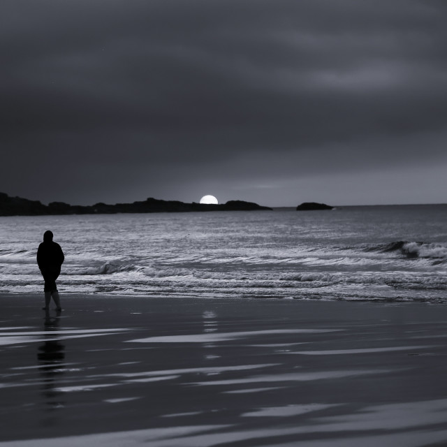 """Silhouette of Man Walking Alone on Beach During Sunset"" stock image"