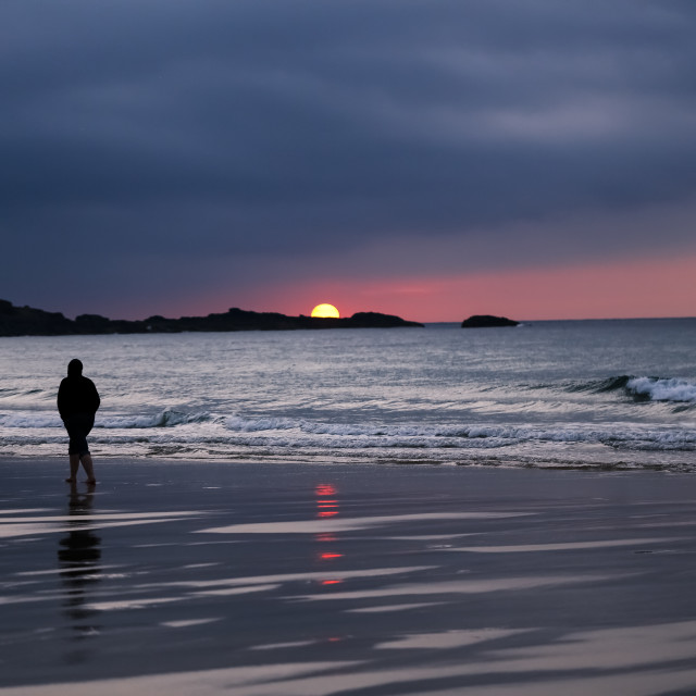 """Silhouette of Man in Hoodie Walking Alone on St Ives Beach During Sunset"" stock image"
