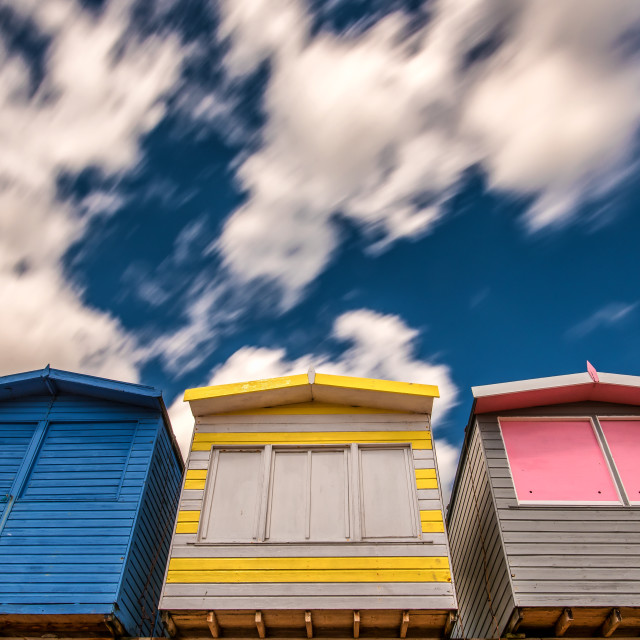 """""""Passing Clouds Over Beach Huts of Frinton"""" stock image"""