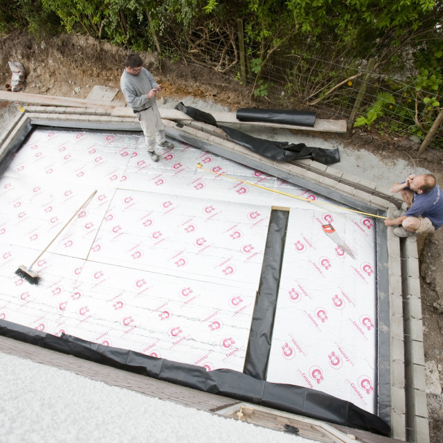 """""""Builders lay under floor insulation into a house extension in Ambleside, UK."""" stock image"""