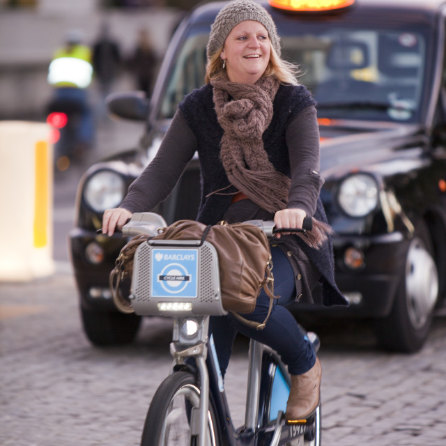 """Women riding a Barclays Cycle Hire scheme, or Borris Bike, part of a green..."" stock image"