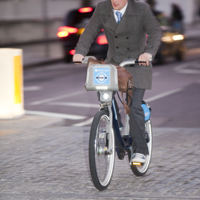 """A business man riding a Barclays Cycle Hire scheme, or Borris Bike, part of a..."" stock image"