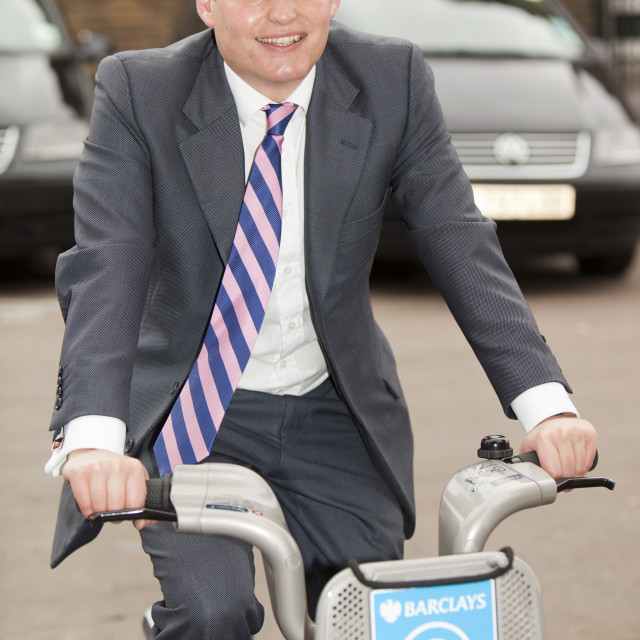 """A Business man on a Barclays Cycle Hire scheme, or Borris Bike, part of a..."" stock image"