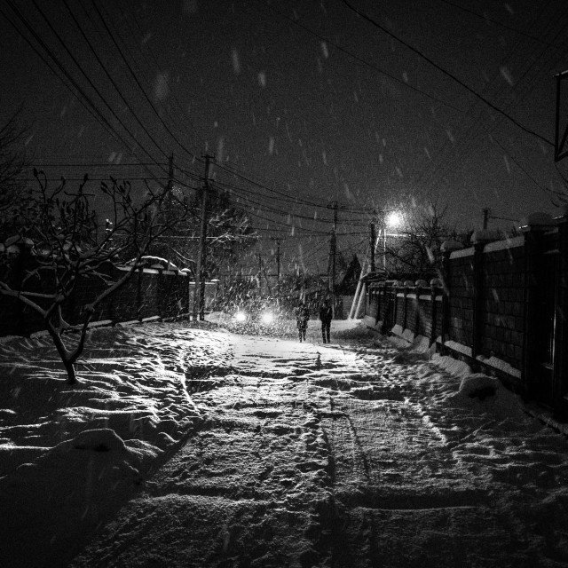 """""""Car headlights and two figures in a blizzard, Bishkek Kyrgyzstan."""" stock image"""