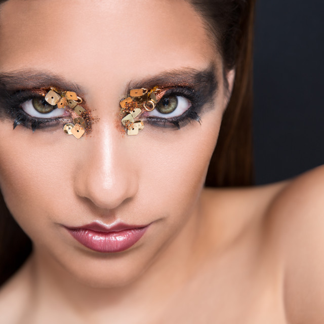 """Head shot of a beauty model with extravagant make up with her eyes open"" stock image"