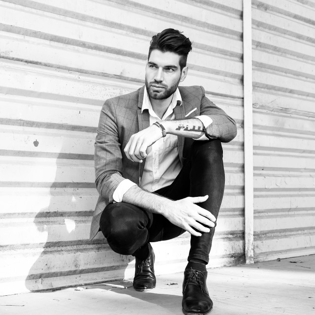 """A male fashion model crouching down in an urban setting in a black and white photograph"" stock image"