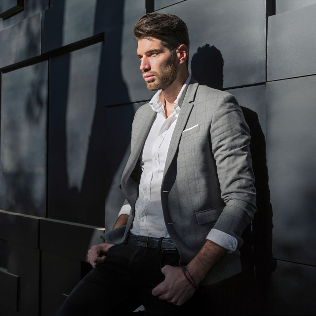 """A male fashion model standing against the wall in a grey jacket and white shirt"" stock image"
