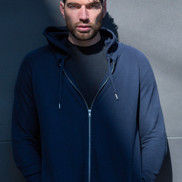 """A male fashion model wearing a blue hoodie standing in a diagonal shadow in an urban setting"" stock image"