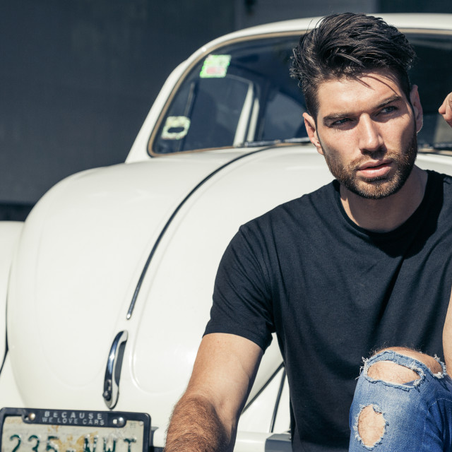 """A male fashion model sitting next to a classic VW Beetle in a urban fashion shot"" stock image"