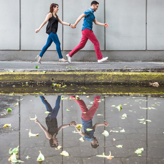 """A latin couple running across a pavement with their reflection in a puddle"" stock image"