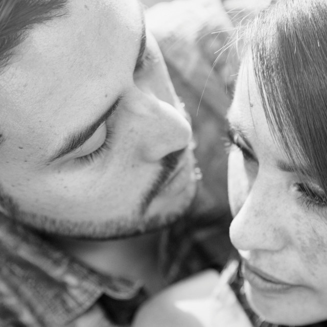 """Black and white portrait of a couple looking at one another intimately and closely"" stock image"