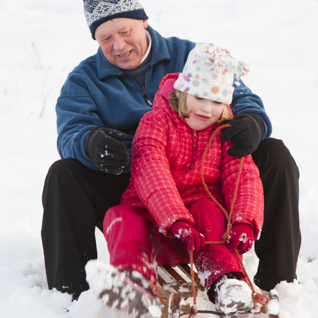 """""""A grandfather sledging with his grand daughter in Ambleside, Lake District, UK."""" stock image"""