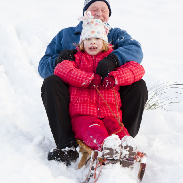 """A grandfather sledging with his grand daughter in Ambleside, Lake District, UK."" stock image"