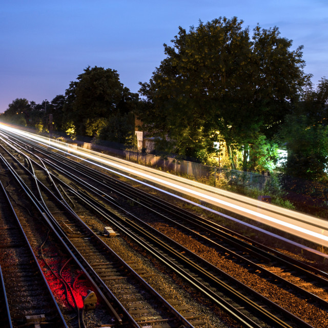 """A trace of light is left by a passing commuter train at dusk in south London, UK."" stock image"