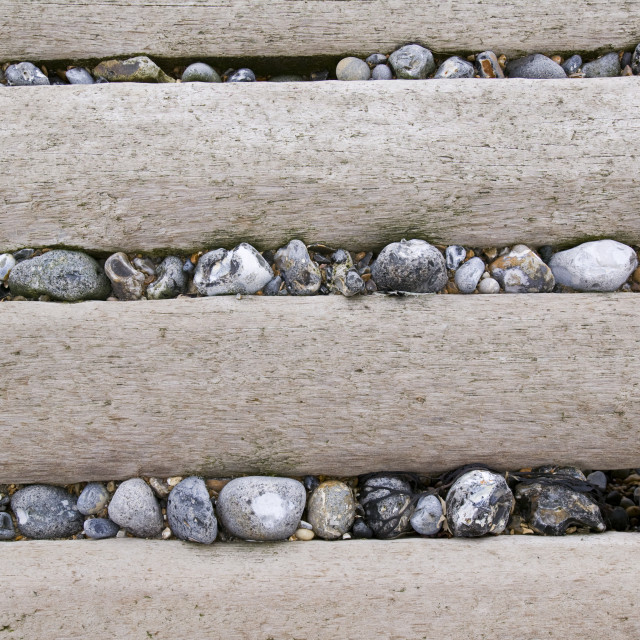 """Flint cobbles in a groyne on a Norfolk beach"" stock image"