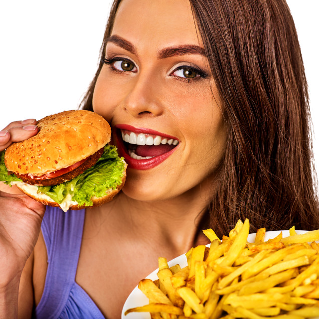 """Woman eating french fries and hamburger on table."" stock image"