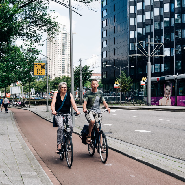 """Two unidentified couple riding their bicycles in a street"" stock image"