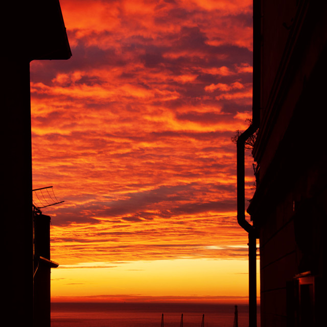 """""""red cloudscape at sunset on the quiet sea harbor, view framed by two house..."""" stock image"""