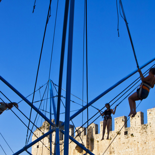 """""""Girls play bungee jumping near medieval castle in Trogir"""" stock image"""