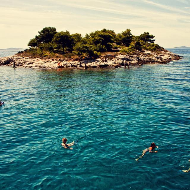 """Croatia,tourists swim near a small island"" stock image"