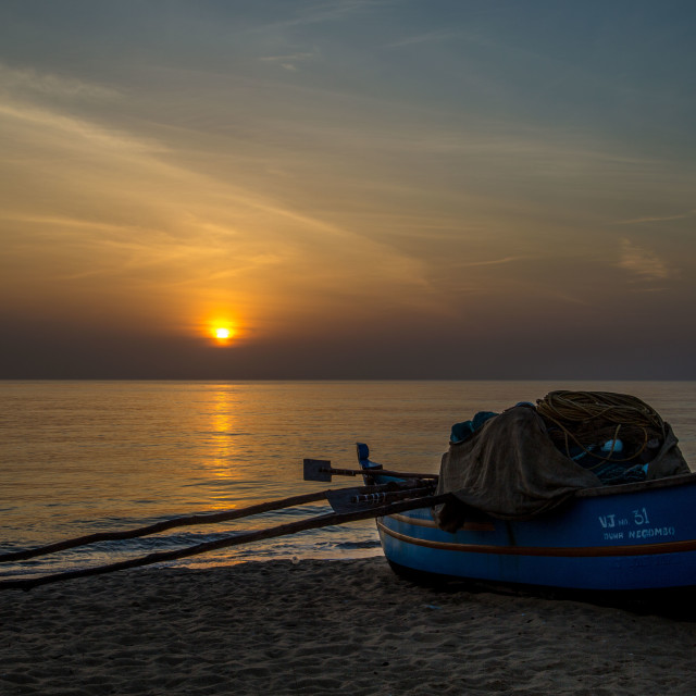 """Fishing boat on beach during Sun Rise 