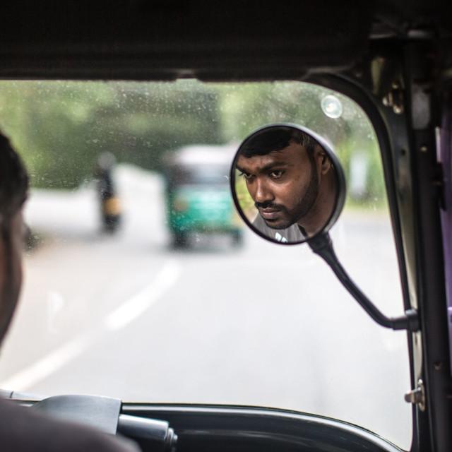 """Reflection of mans face in Tuk Tuk Taxi, Sri Lanka"" stock image"