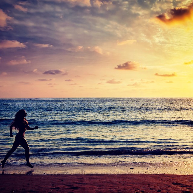 """Beautiful athletic woman running along sea on the beach"" stock image"