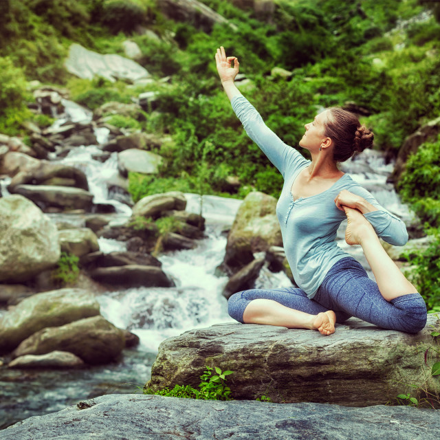 """Sorty fit woman doing yoga asana outdoors at tropical waterfall"" stock image"