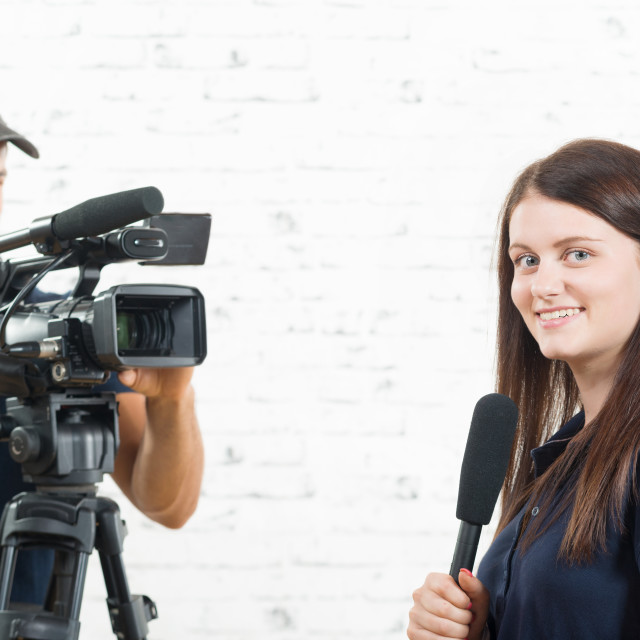 """""""a young journalist with a microphone and a cameraman"""" stock image"""