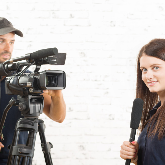 """""""a young woman journalist with a microphone and a cameraman"""" stock image"""