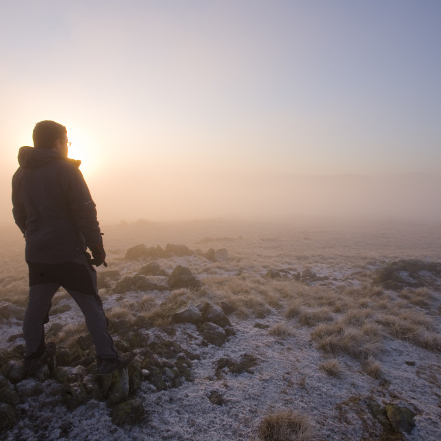 """""""A walker on the summit of Caudale Moor at sunset in the Lake District UK"""" stock image"""