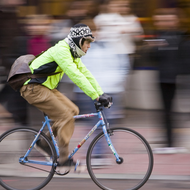 """""""City workers wait to cross the road in london with a cyclist speeding by"""" stock image"""