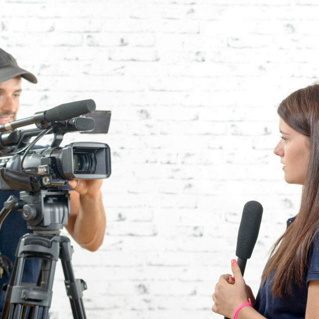 """""""young woman journalist with a microphone and cameraman"""" stock image"""