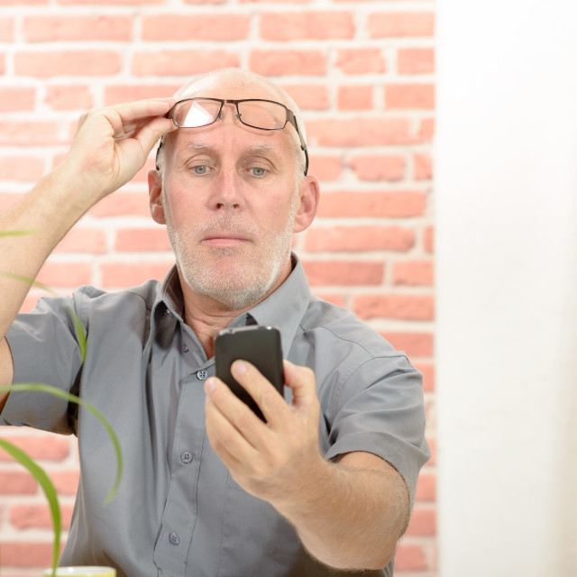 """Mature man having trouble seeing phone screen because of vision problems"" stock image"