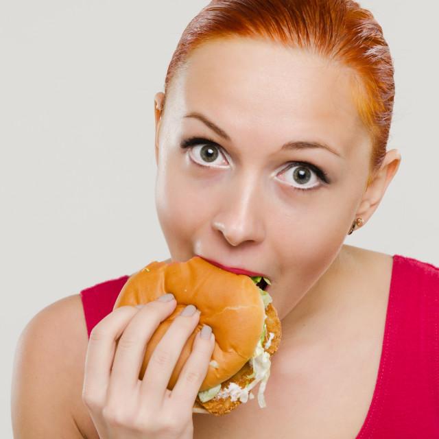 """""""Woman eating hamburger"""" stock image"""