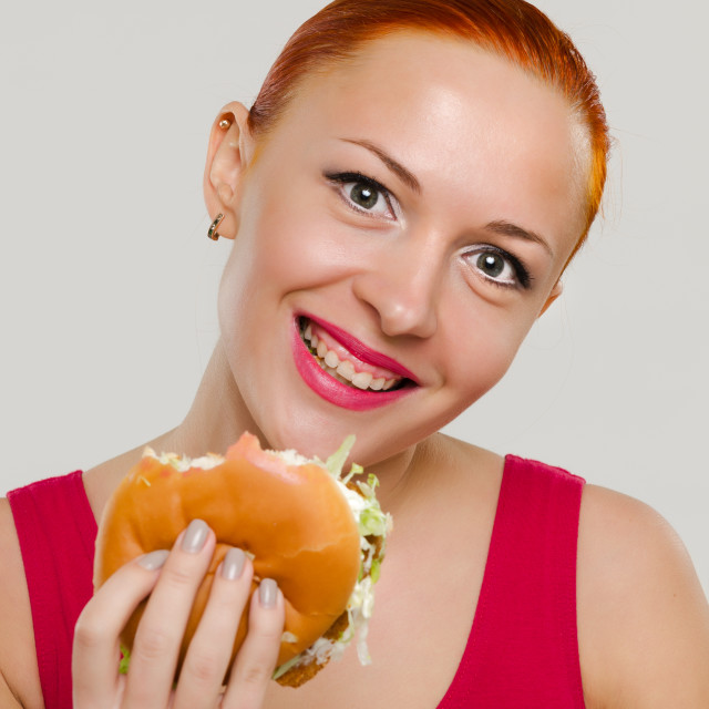 """Smiling woman with hamburger"" stock image"