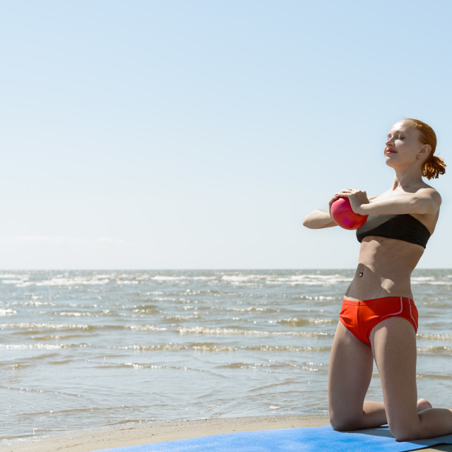 """Beautiful woman practicing fitness by the sea"" stock image"