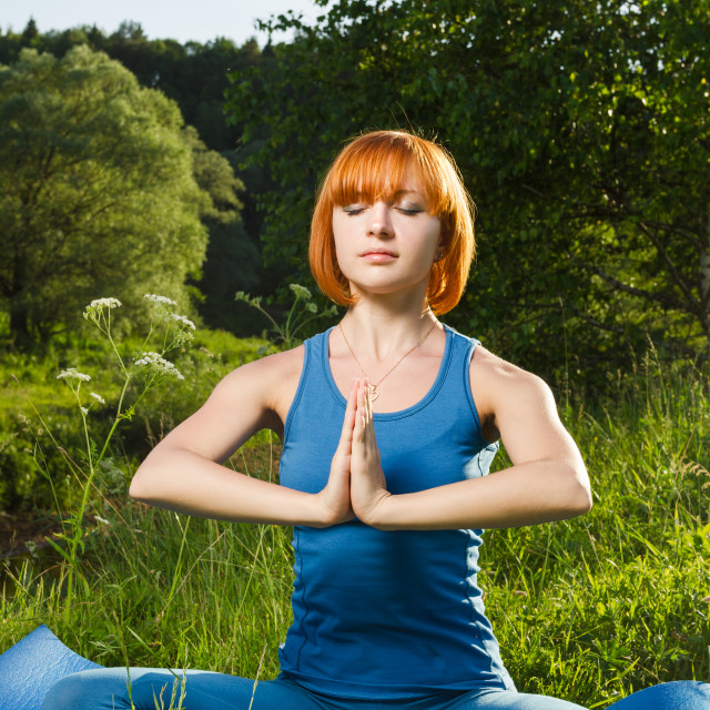 """Red woman meditating outdoors"" stock image"