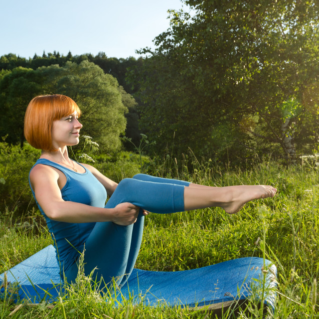 """Red woman practicing fitness yoga outdoors"" stock image"