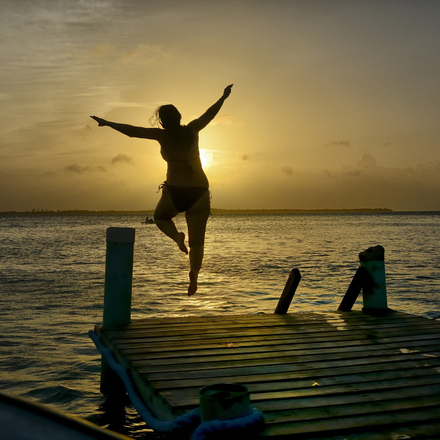 """Woman jumps from a pier at sunset"" stock image"