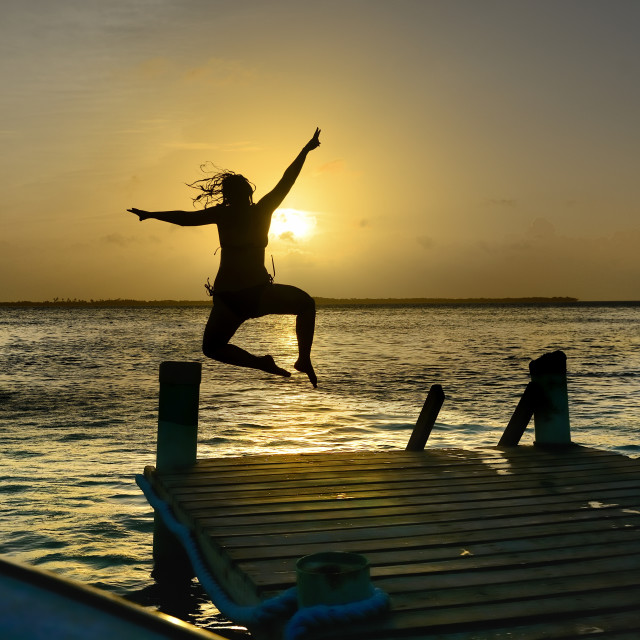 """Woman leaps into the sea at sunset"" stock image"