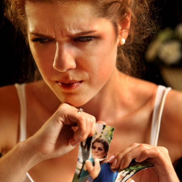 """""""Sad bride on unhappy wedding. Portrait girl tearing family pictures."""" stock image"""