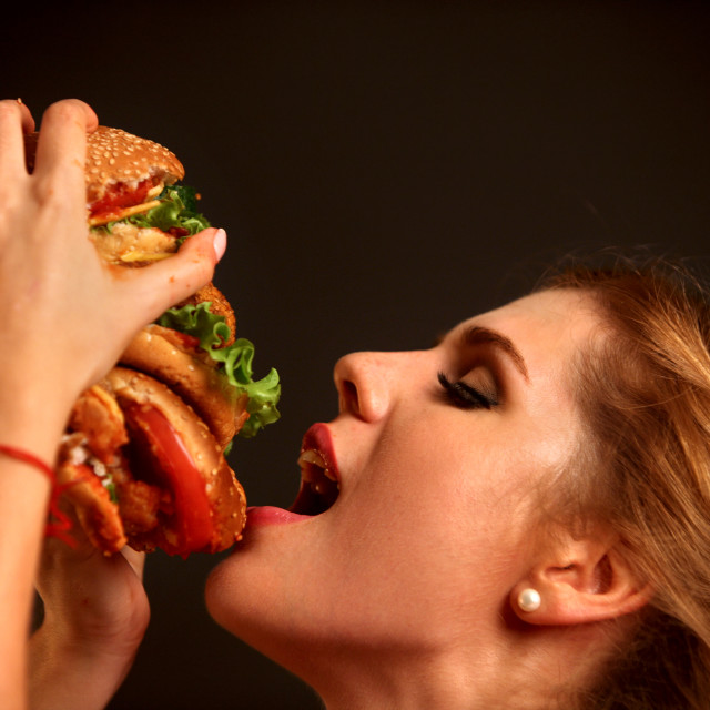 """Woman eating hamburger. Student consume fast food."" stock image"
