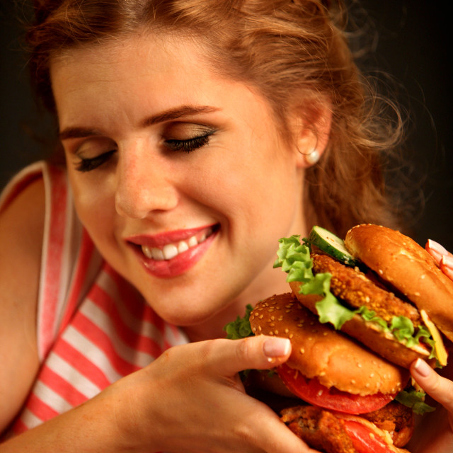 """Woman eating burger and winks. Happy student eat sandwich lunch."" stock image"