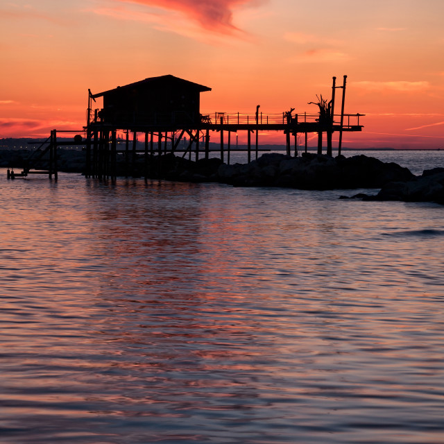 """""""Stilt house in silhouette over the sea"""" stock image"""