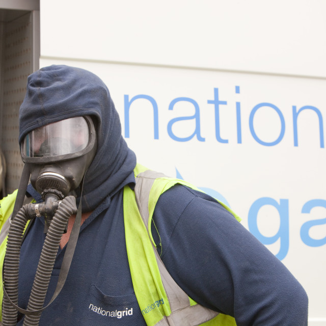 """A Britiush Gas worker wears protective gas mask prior to cutting through the..."" stock image"